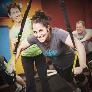 Woman suspended from TRX straps.